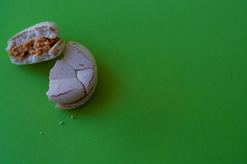 One broken macaron tastefully salted caramel on one-ton green background. French dessert. Sweets.