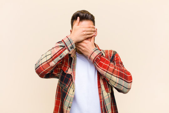 young hispanic man covering face with both hands saying no to the camera! refusing pictures or forbidding photos against isolated background