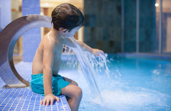 4 years boy playing with jets at indoor pool SPA