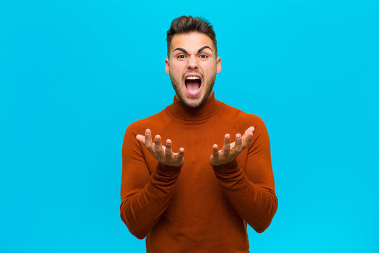 young hispanic man looking desperate and frustrated, stressed, unhappy and annoyed, shouting and screaming against blue background