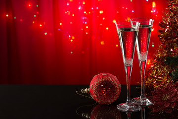 Two champagne glasses and red Christmas ball on a reflective surface on a red background. Christmas bright background. The form is ready to add text or a picture.
