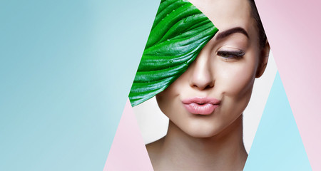 Fototapeta Portrait of young beautiful woman with healthy glow perfect smooth skin holds green tropical leaf. Model with natural nude make up look into the hole of pink, blue paper. obraz