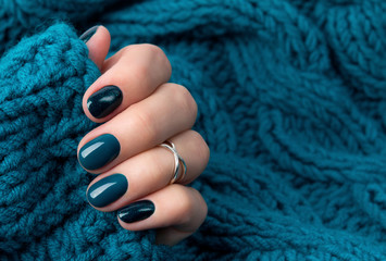 Fotobehang Manicure Manicured woman's hand in warm wool turquoise sweater