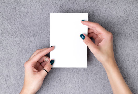 Manicured woman's hands holding postcard on grey furry background