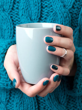 Woman's hands with turquoise manicure hold a grey cup of coffee or tea
