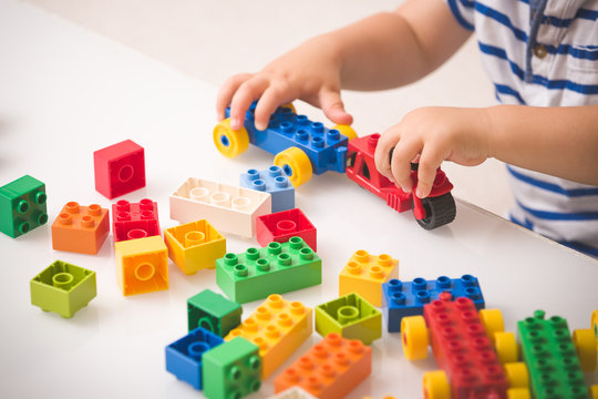 Toddler child playing multi-colored cubes on the table. Colorful plastic bricks for the early development of the child. Early learning and educational toys for a little boy