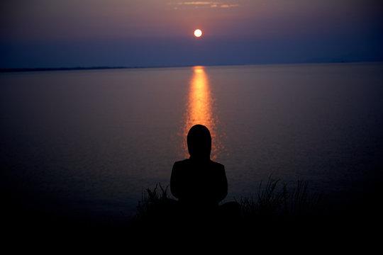 Woman meditating about Baikal Lake at sunruse time