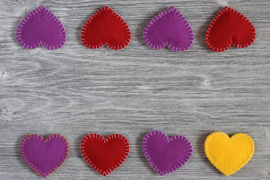 Red, purple and yellow felt handmade volume hearts on gray wooden background. Love, romance, valentine day concept. Top view. Flat lay