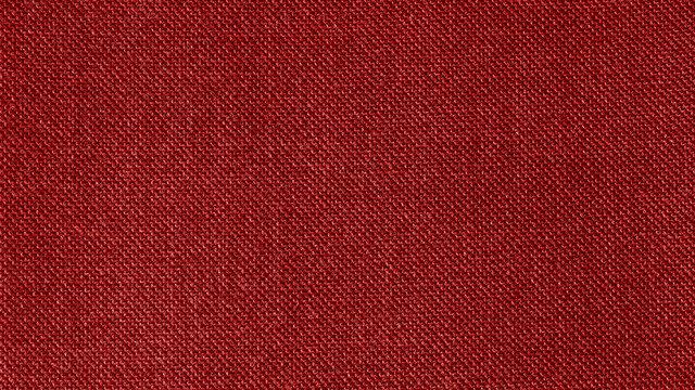 Dark red woven fabric texture background. Closeup