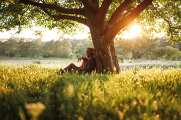 Bearded man relaxing under tree in nature Wall mural