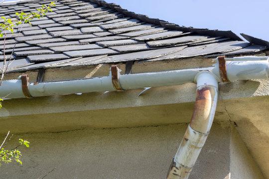 Old gutter. A broken gutter on the roof of a house