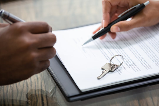 Businessman Signing Contract With Keys On It