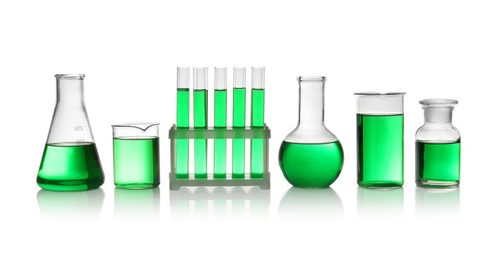 Laboratory glassware with green liquid on white background