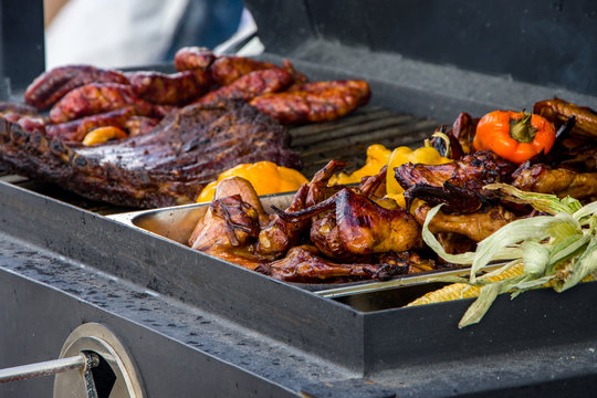 Meat and vegetables are grilled on the kitchen's large trailer grill, chicken wings and meat ribs
