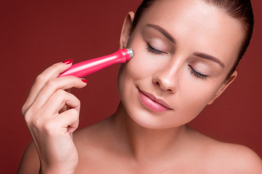 Beautiful brunette woman massage her face with a beauty massager. Her skin fresh, clean and flawless. Spa procedure concept