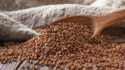 Fototapeta Rural still-life - the peeled groats of buckwheat (Fagopyrum esculentum) on the background of burlap, closeup with selective focus obraz