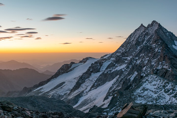 Beautiful early morning sunrise view of Portjenhorn mountain and Pizzo d'Andolla in the Weissmies Group of the Valais Alps in Switzerland. Seen from Zwischenberg Pass on the way up to Weissmies peak.