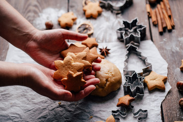 Christmas bakery. Freshly baked homemade gingerbread cookies, dough cutters, rolling pin and food decorations on the table.Family festive culinary and New Year traditions concept