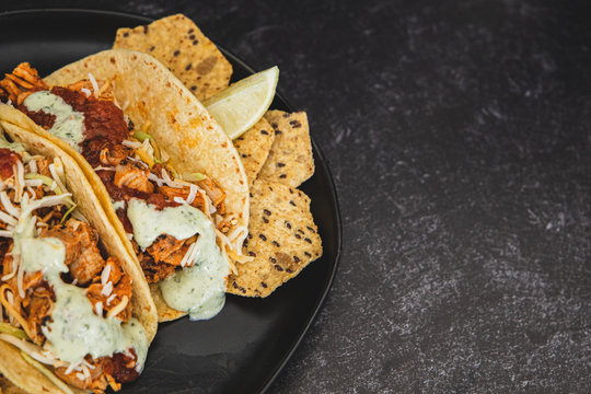 Mexican fresh chicken tacos with cabbage, cheese and cilantro cream sauce in a flour tortilla with multigrain corn tortilla chips