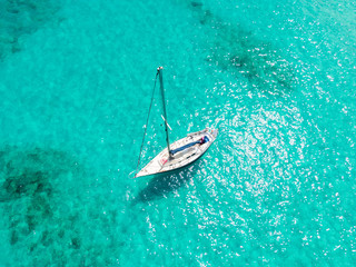 High angle aerial drone bird's eye view of a sailing yacht with sails lowered anchored in shallow, turquoise water in the Atlantic Ocean near the coast of Fuerteventura, Canary Islands, Spain, Europe.