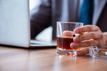 Male employee drinking alcohol and smoking cigarettes at workpla