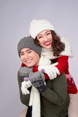 Happy young lovers in knitted woolen clothing hugging and looking together.