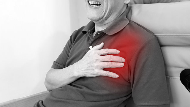 Elderly man suffering from chest pain with painful facial expression. Chest pain symptom may be from emergency heart disease as angina, myocardial infarction, acute coronary syndrome disorder.