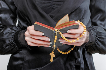 Widow in black dress holds a rosary and The Holy Bible in her hands.