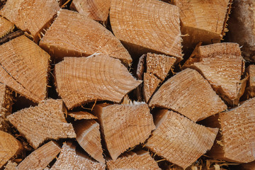 An array of firewood for burning in a stove is piled close-up.