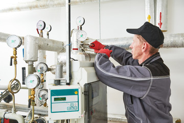 heating engineer or plumber in boiler room installing or adjusting manometer