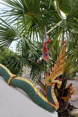 Detail of the end of a decorative stair railing sculpted in the form of a dragon at a Buddhist temple in Thailand with a background of tropical palm leaves.