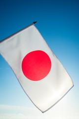 Japanese flag hanging backlit in front of bright blue sky