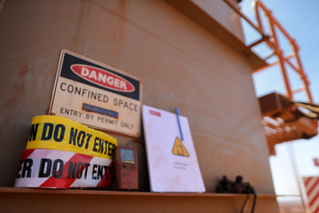 Warning barricade danger tape, caution tape with defocused gas leak test atmosphere detector at confined space permit at manhole entry door and permit book template at the background construction site