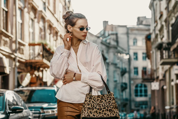 Outdoor autumn fashion portrait of elegant, luxury lady wearing sunglasses, trendy white shirt, wrist watch, holding animal, leopard print bag, posing in street of European city. Copy, empty space