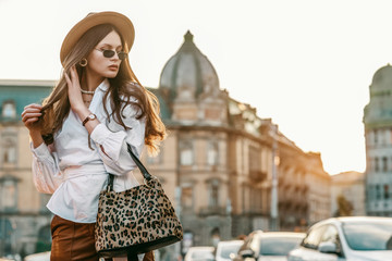 Outdoor fashion portrait of elegant, luxury woman wearing beige hat, sunglasses, trendy white shirt, brown wrist watch, holding animal, leopard print bag, posing in street. Copy, empty space for text