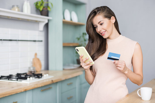 Young woman holding credit card and using smart phone at home. Online shopping, spending money, enjoying life concepts
