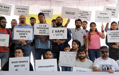 People hold placards during a protest against the ban on the sale, import and manufacture of e-cigarettes by the Indian government, in New Delhi