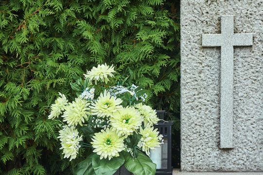 A bouquet of autumn chrysanthemum flowers and a stone cross on a grave.
