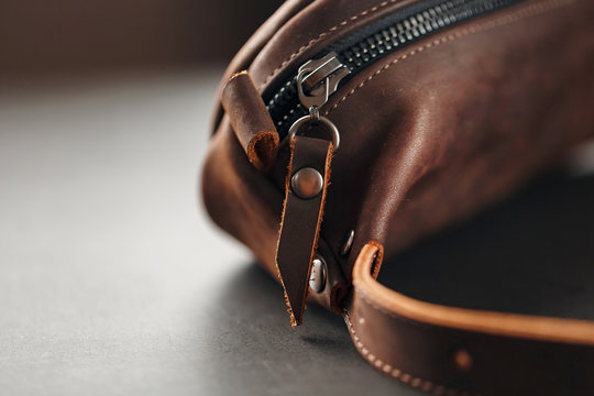 Handmade genuine brown leather on a dark background Brown belt bag. Elegant brown bag with a zipper