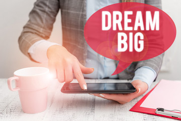 Text sign showing Dream Big. Business photo showcasing To think of something high value that you want to achieve Business woman sitting with mobile phone and cup of coffee on the table