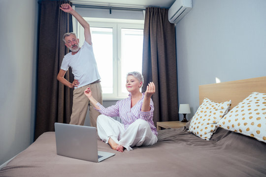 blonde short haircut woman meditating with laptop yoga video teacher in nightwear and elderly man doing stretching hands,spine in day light bedroom apartment