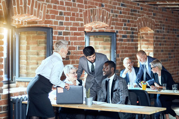 In the foreground two blonde caucasian women, caucasian bearded brunette man, african man talk. On the background two blonde caucasian men and one woman at table.