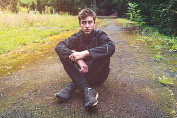 sad young man sitting on the road with crossed legs