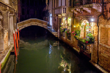 Fototapete - Venice at night, Italy. Beautiful narrow canal with bridge and vintage houses. Old street in Venice city with cafe or restaurant at dusk. Architecture of Venice in summer evening. Travel concept.