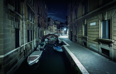 Fototapete - Venice city at night, Italy. Narrow canal with boats and vintage houses at dusk. Traditional Venice street in twilight. Romantic stroll across Venice in evening. Cityscape of old European town.