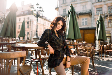 Beautiful happy smiling girl with dark hair, nude makeup, wearing stylish black jacket posing in street cafe. Outdoor portrait, day light. Female autumn fashion concept. Copy, empty space for text Wall mural