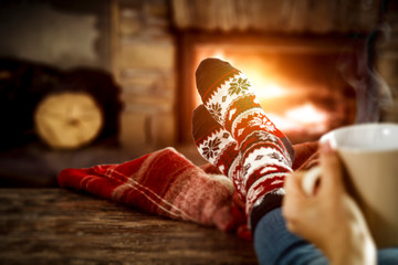 Fireplace and slim woman legs with christmas socks