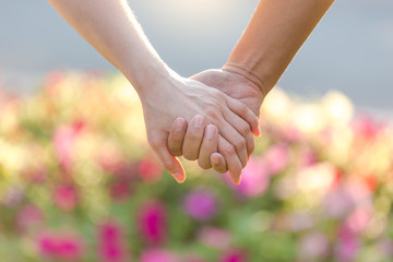 Closeup of loving couple holding hands while walking in the park