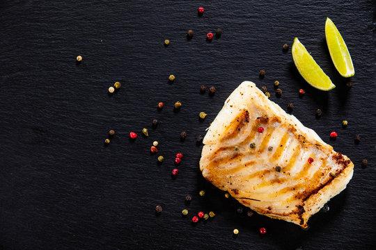 Fried cod loin on black stone plate