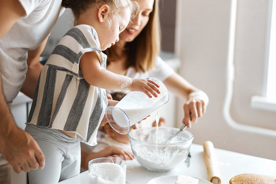 cute girl adding milk to a bowl with dough, close up cropped side view photo